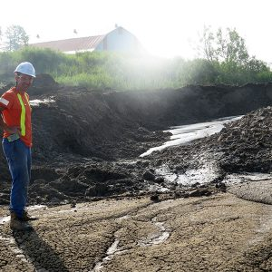 Aecon Case Worker Operator standing on solidified mud